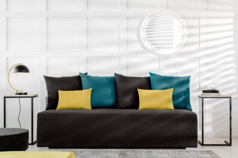 Jak yin i yang – czarna sofa Maringa na tle białej ściany.