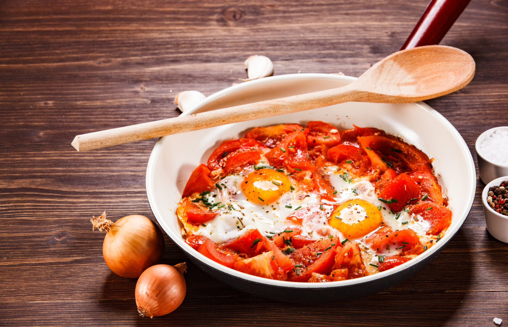 Shakshuka - fried eggs with vegetables in frying pan