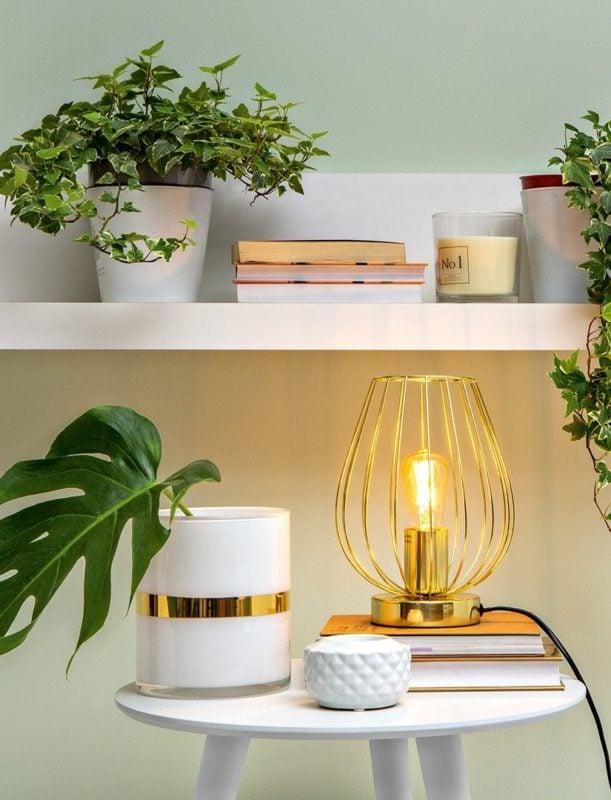 La lampe de table Anika Gold illuminera parfaitement les étagères d'une chambre moderne.